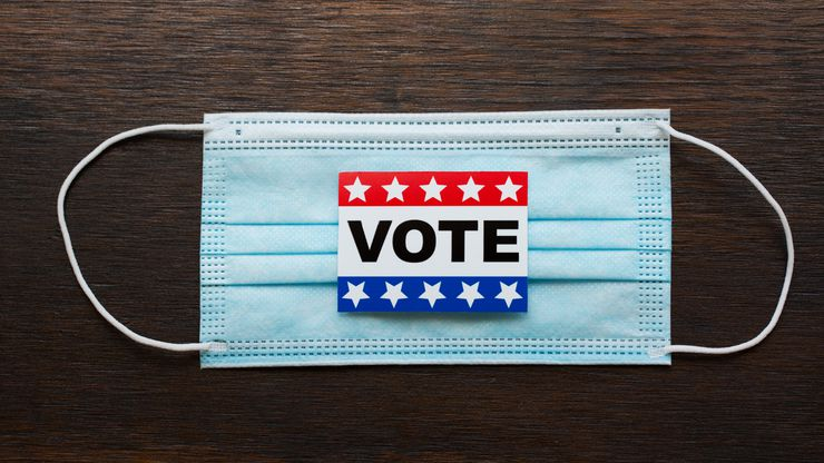 Vote sticker on face masks and american flags