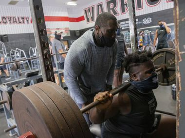 "Homicide Sergeant Brian Jones (left) from the Arlington Police Department spots for Arlington Martin Defensive tackle Marquis Evans during their workout at the school's gym as part of the ""Coach 5-0"" program on Monday, Sept. 21, 2020 in Arlington. (Juan Figueroa/ The Dallas Morning News)"