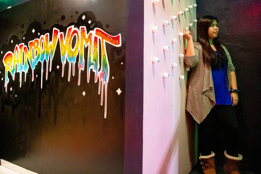 Renee Ng plays with an eyeball on a wall during a soft opening night at Rainbow Vomit on Thursday, Jan. 17, 2019. Rainbow Vomit is a new immersive art installation that will open on Saturday, January 19, 2019. (Shaban Athuman/The Dallas Morning News)