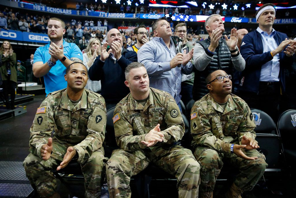 (from l to r) Staff sergeants Michael Reed, Zach Johnson and Scotty Scruggs look up as the arena applauds for the soldiers in attendance at the Seat for Soldiers annual game between the Dallas Mavericks and Utah Jazz at American Airlines Center in Dallas on Wednesday, November 14, 2018. (Vernon Bryant/The Dallas Morning News)
