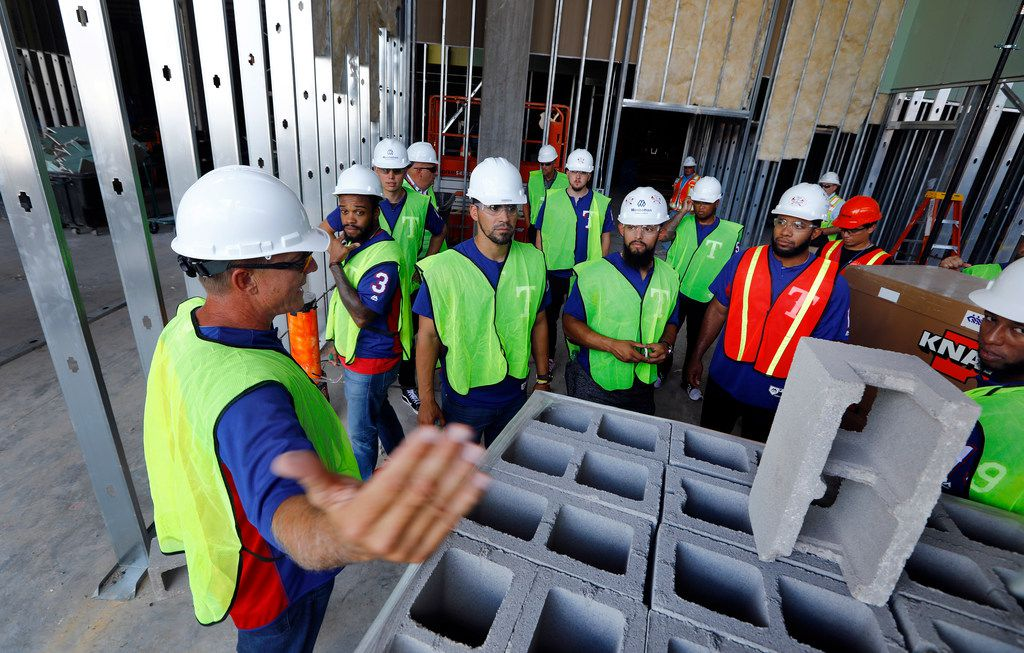 Texas Rangers manager Jeff Banister (left) shows the work out room to his players as they toured the new Globe Life Field under construction in Arlington, Texas, Tuesday, September 18, 2018. The Texas Rangers celebrated the One Million Man Hours by providing a barbecue lunch for it's nearly 900 construction workers. Rangers baseball players joined manager Jeff Banister in handing out construction helmet stickers to mark the occasion. They also signed autographs and posed for photos.