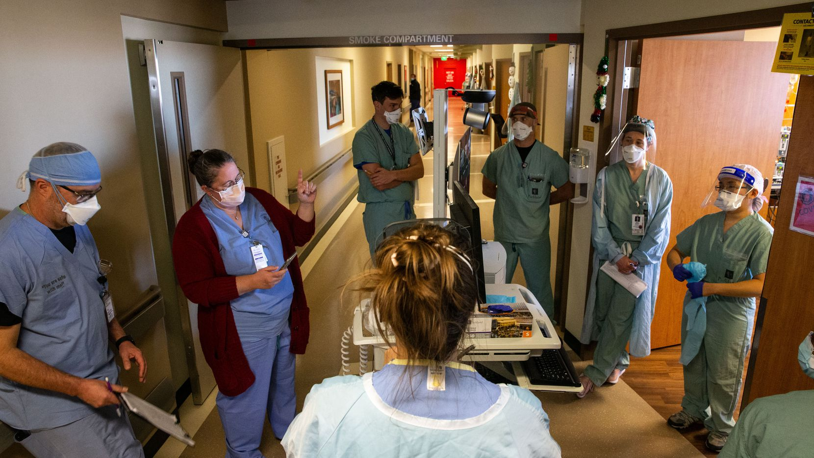 """Rowley (second from left) huddles with Dr. Catherine Chen (right) and other staff members on the Progressive Care Unit of Parkland's COVID-19 Tactical Care Unit. Rowley and Chen were assessing the level of care for patients to determine whether they should be upgraded to the Intensive Care Unit or downgraded out of the TCU. """"I anticipate things are going to go poorly,"""" Rowley said, referencing high travel numbers over the Thanksgiving holiday. """"There's not going to be a single thing we can do to stop it. And all we can do is hope that we can keep enough people alive that can defeat this disease."""""""