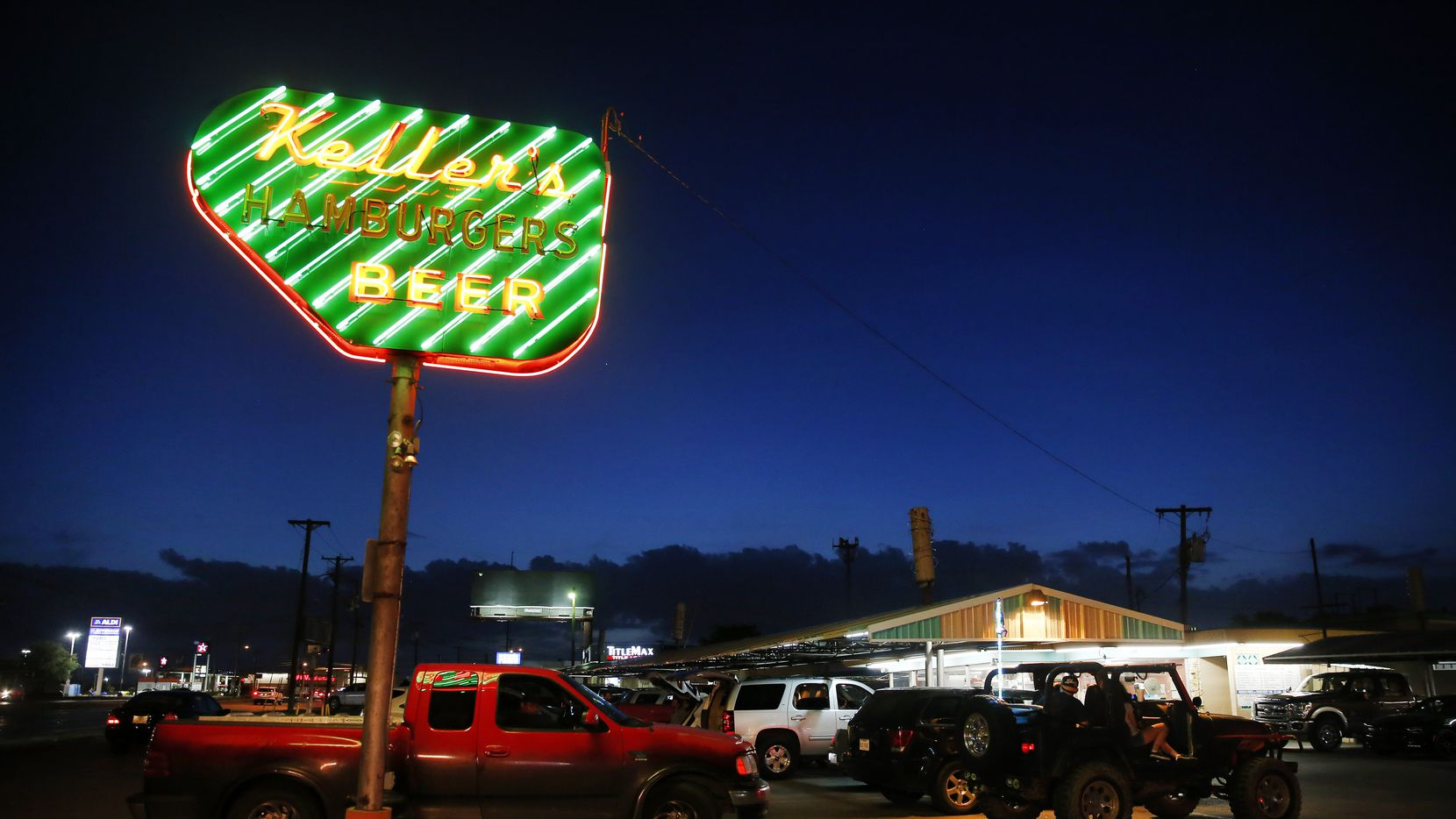 At dusk, the neon sign at Keller's Drive-In glows on Northwest Highway in Dallas.