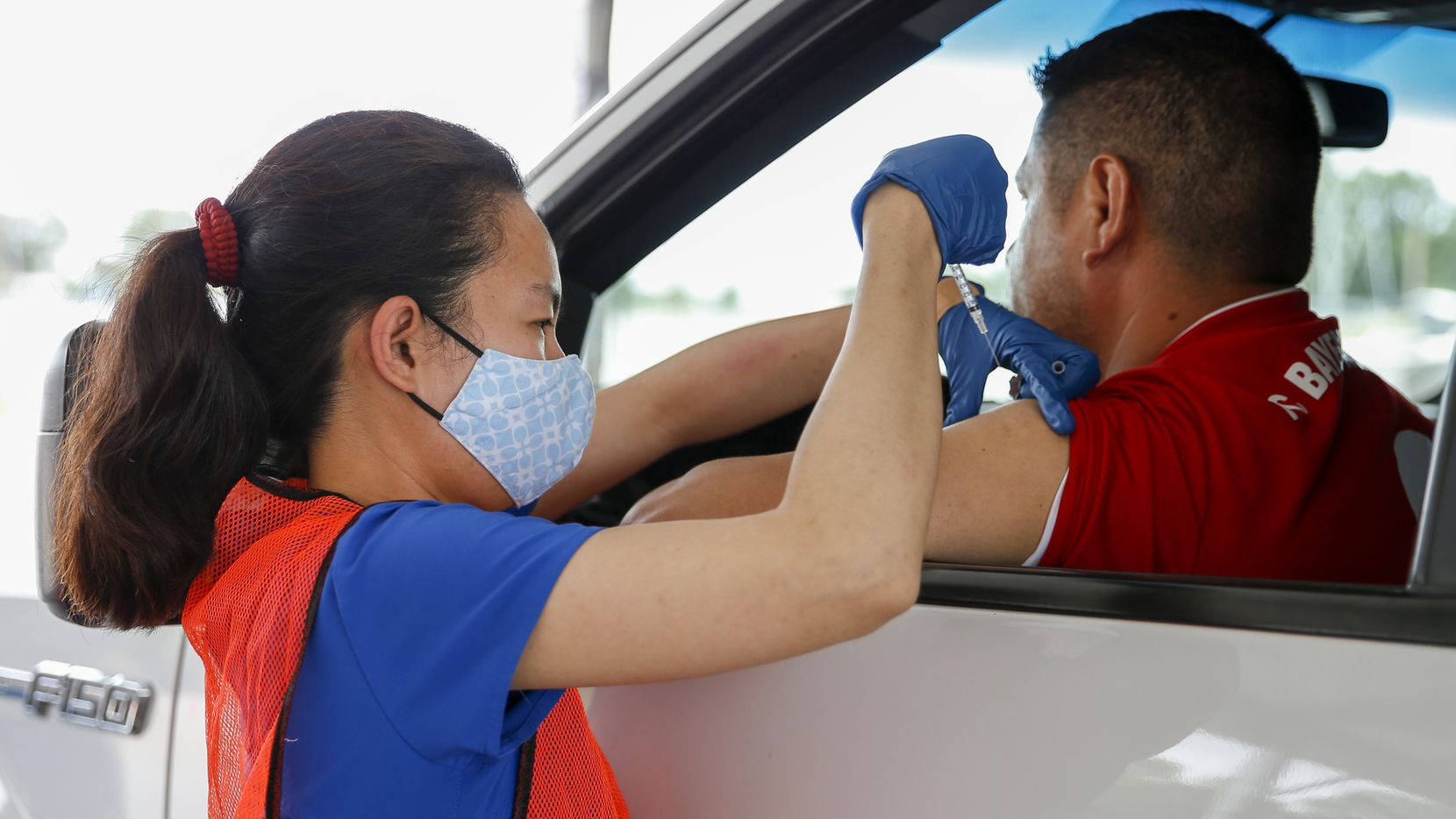 Registered nurse Christine Atayde administers a dose of the COVID-19 vaccine during the last day of vaccinations at the drive-thru Fair Park site on Saturday, July 17, 2021, in Dallas. More than 12,000 doses could be administered at the site during its peak. (Elias Valverde II/The Dallas Morning News)