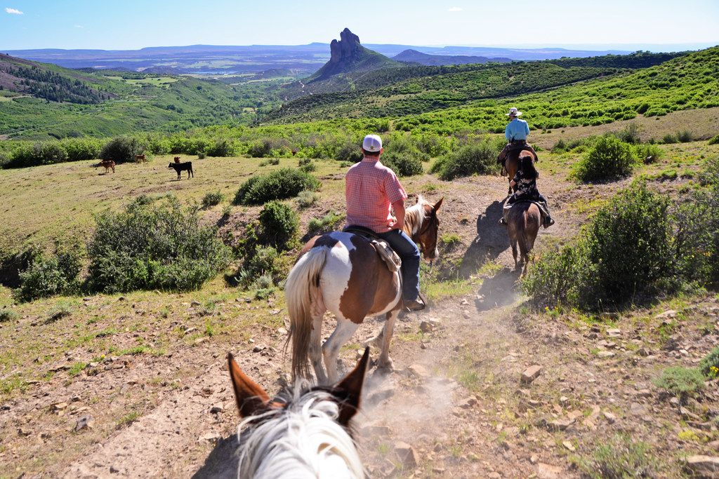 Guests ride on a trail at Smith Fork Ranch with the unique Needle Rock in the background.
