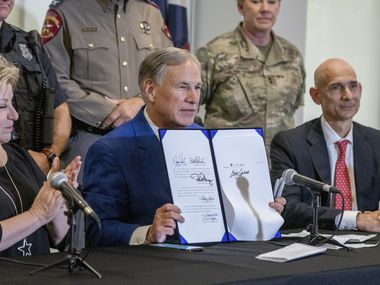 Flanked by Senator Jane Nelson and Representative Greg Bonnen, Texas Governor Greg Abbott, center, holds up HB9 after signing it at a press conference at the Fort Worth Police Officers Association headquarters on Friday September 17, 2021.
