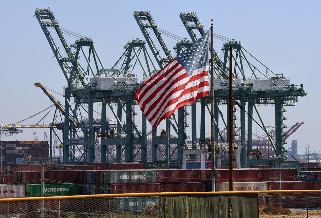 The U.S. flag flies over Chinese shipping containers unloaded at the Port of Long Beach on Sept. 29, 2018.