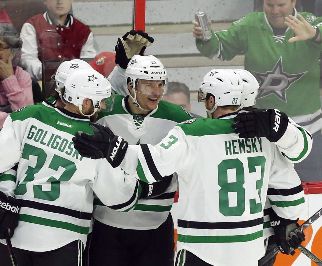 Dallas Stars' Antoine Roussel (21) celebrates his game-winning goal against the Ottawa Senators with teammates Alex Goligoski (33) and Ales Hemsky (83) during third period NHL hockey action, in Ottawa on Sunday, March 6, 2016. (Fred Chartrand/The Canadian Press via AP)