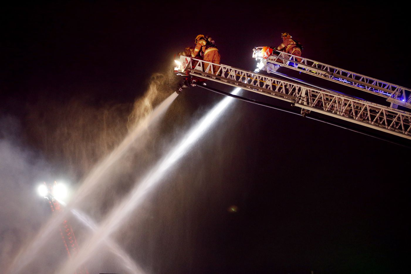 Dallas firefighters using aerial ladders battle a four-alarm business fire in the Fair Park area, just south of Interstate 30 near the Austin Street Shelter, Wednesday, November 13, 2019. Smoke was seen rolling across Interstate 30 from the ORS Food Company. (Tom Fox/The Dallas Morning News)
