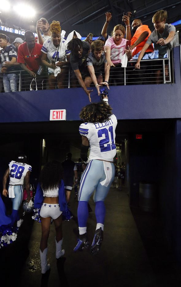 Dallas Cowboys running back Ezekiel Elliott (21) leaps to high five fans leaning over the tunnel following their win at AT&T Stadium in Arlington, Monday, September 27, 2021. The Cowboys defeated the Philadelphia Eagles, 41-21. (Tom Fox/The Dallas Morning News)