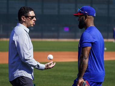 El gerente general de los Texas Rangers, Jon Daniels, juega con una pelota mientras platica con el jugador Danny Santana durante el campamento de entrenamiento en Surprise, Arizona.