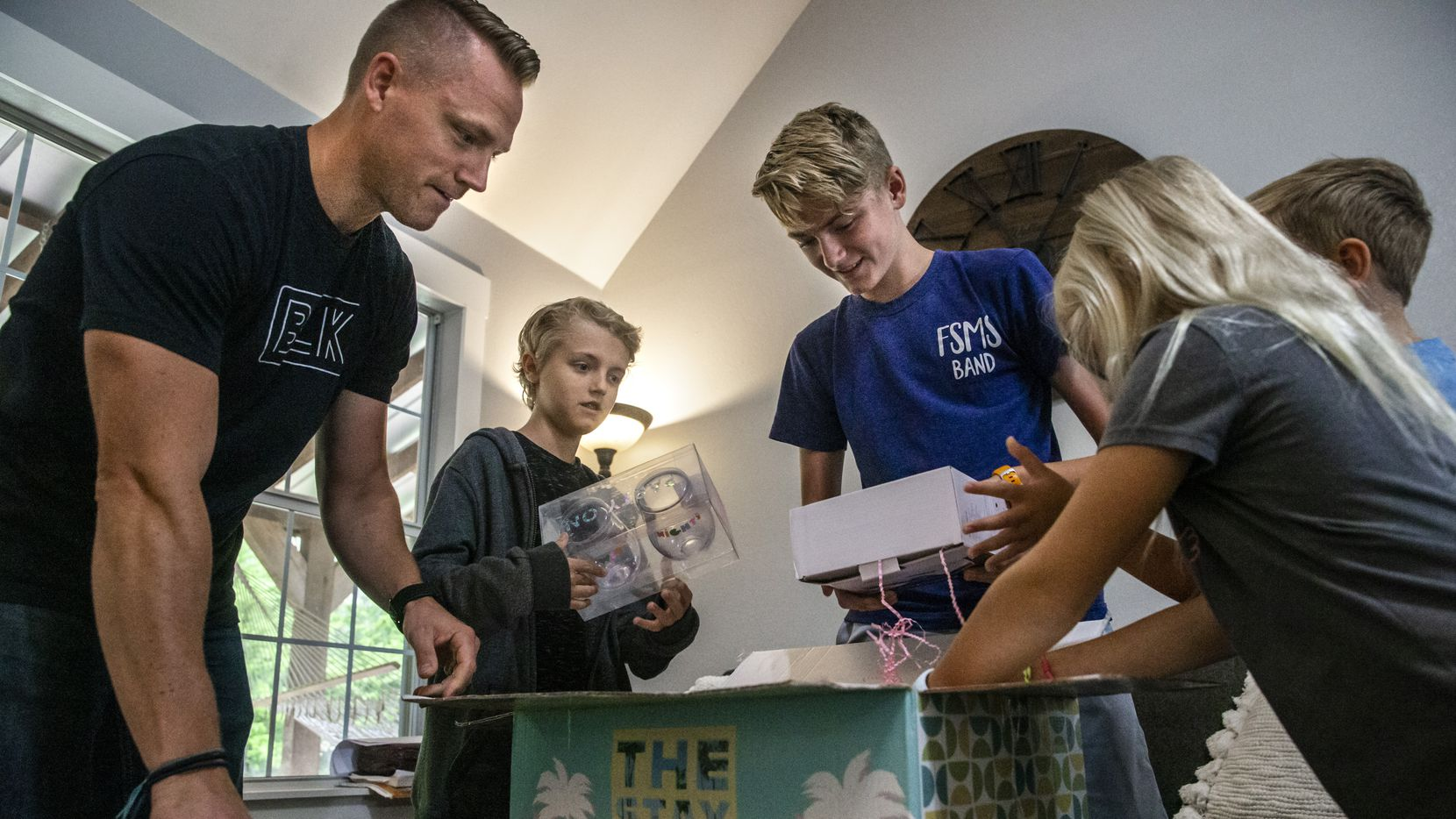 Match.com affinity design team lead James Walker (left) and his children Cade, 11, Boston, 14, Hudson, 9, and Avery, 7, open a themed gift box from the company at their home in Midlothian.
