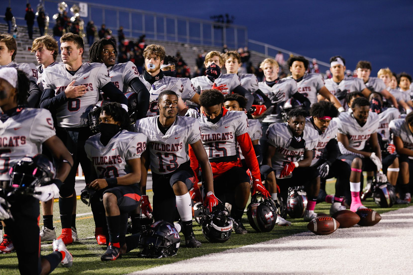 Lake Highlands players kneel and stand during the national anthem before a football game against Irving MacArthur High School at Joy & Ralph Ellis Stadium in Irving on Friday, Oct. 23, 2020. (Juan Figueroa/ The Dallas Morning News)