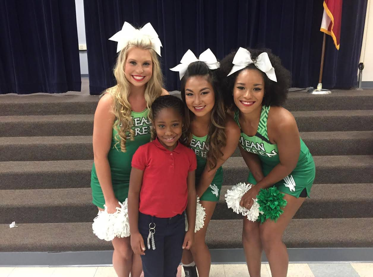Jordin Phipps, 8, posed with University of North Texas cheerleaders after the school assembly at which she was awarded a $10,000 scholarship.