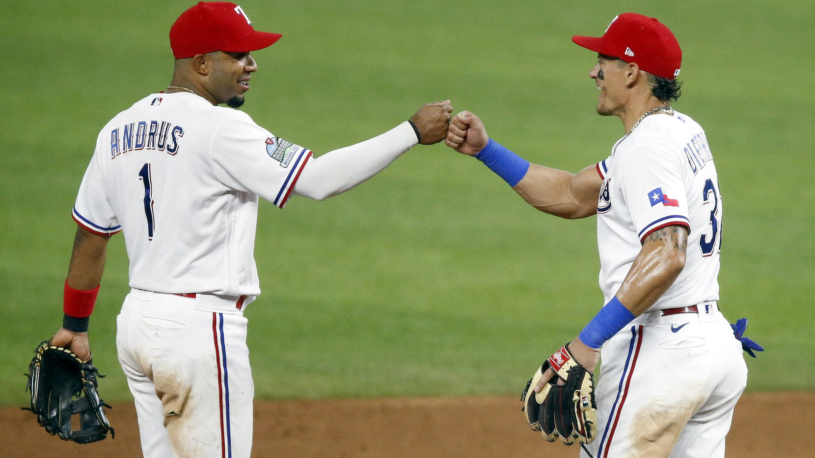 Texas Rangers second baseman Derek Dietrich (32) is congratulated on his good game by shortstop Elvis Andrus (1) after their 7-4 comeback win against the Seattle Mariners at Globe Life Field in Arlington, Wednesday, August 12, 2020.