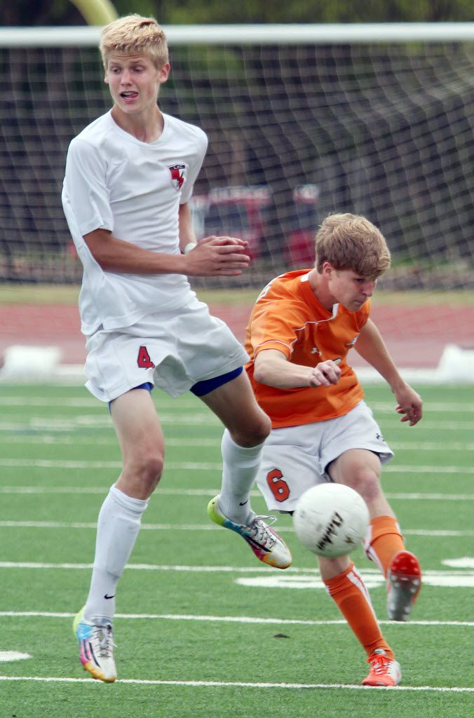 Frisco Wakeland's Dylan Rakestraw (6, right) kicks the ball past Frisco Liberty's Keaton Parks (4, left) in the second half of their playoff game at Standridge Stadium in Carrollton on Saturday, March 12, 2014. (Kelley Chinn/Special Contributor)
