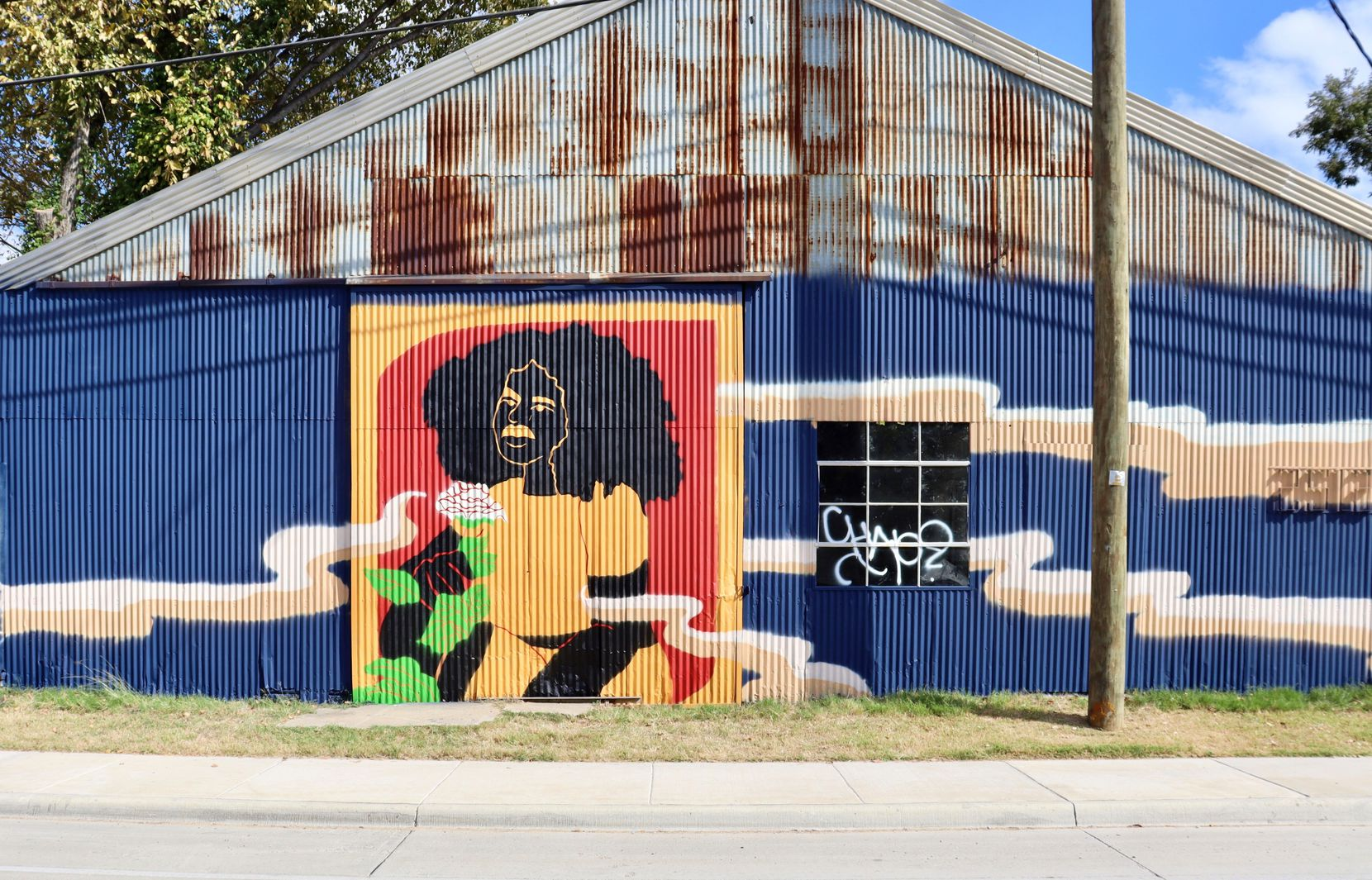 "Artist Desireé Veniecia painted an ArtsBridge mural called ""Black Beauty Is an Act of Resistance"" in West Dallas."