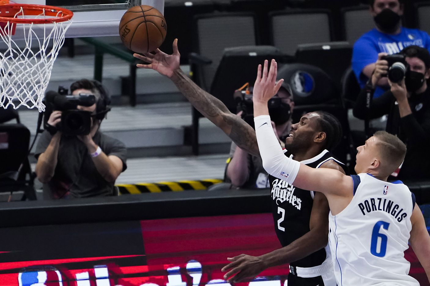 LA Clippers forward Kawhi Leonard (2) scores past Dallas Mavericks center Kristaps Porzingis (6) during the first quarter of an NBA playoff basketball game at American Airlines Center on Sunday, May 30, 2021, in Dallas.