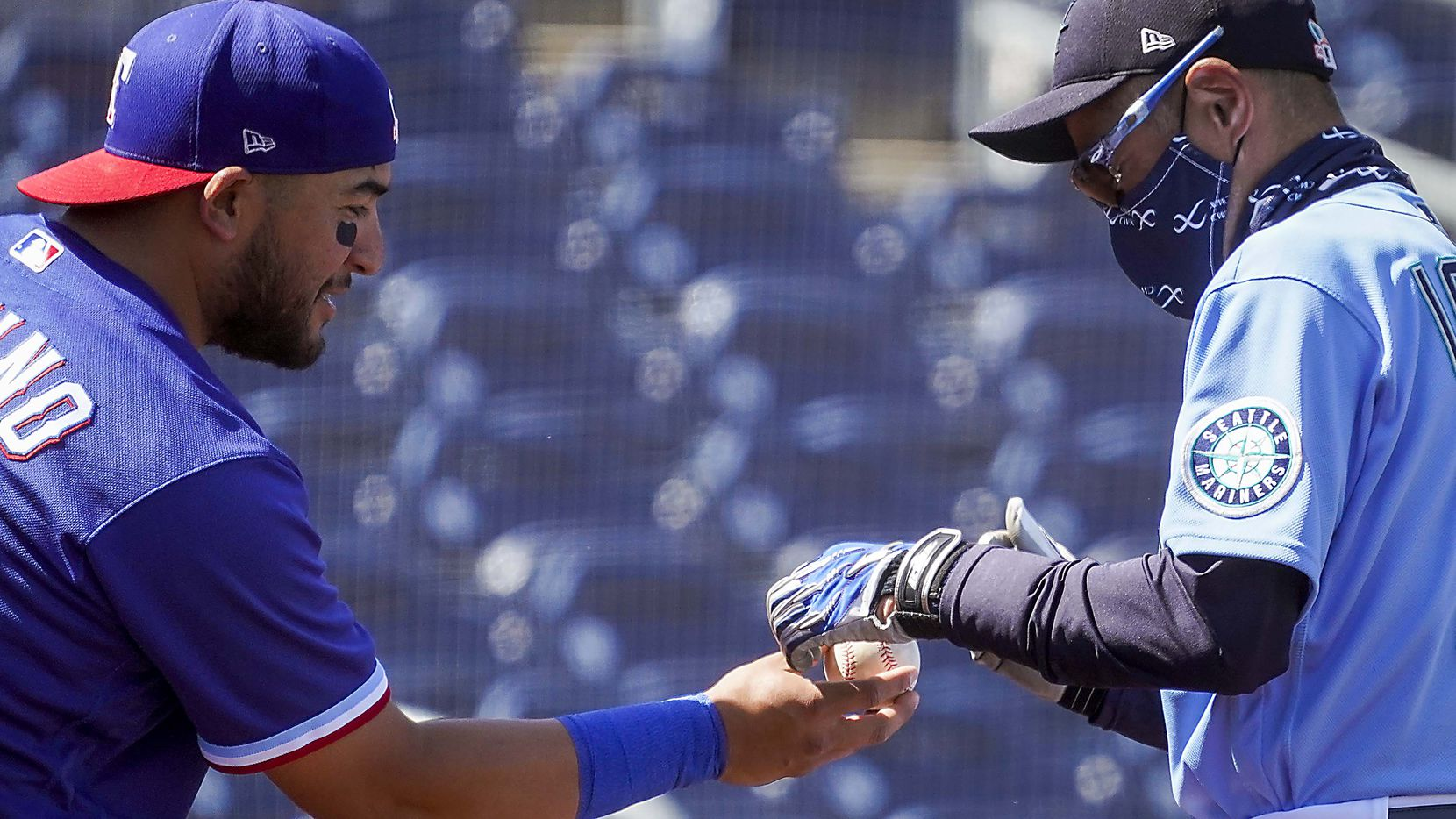 Texas Rangers catcher Jose Trevino hands a ball to Seattle Mariners special assistant to the chairman Ichiro Suzuki to get his autograph before a spring training game at Peoria Sports Complex on Wednesday, March 10, 2021, in Peoria, Ariz.