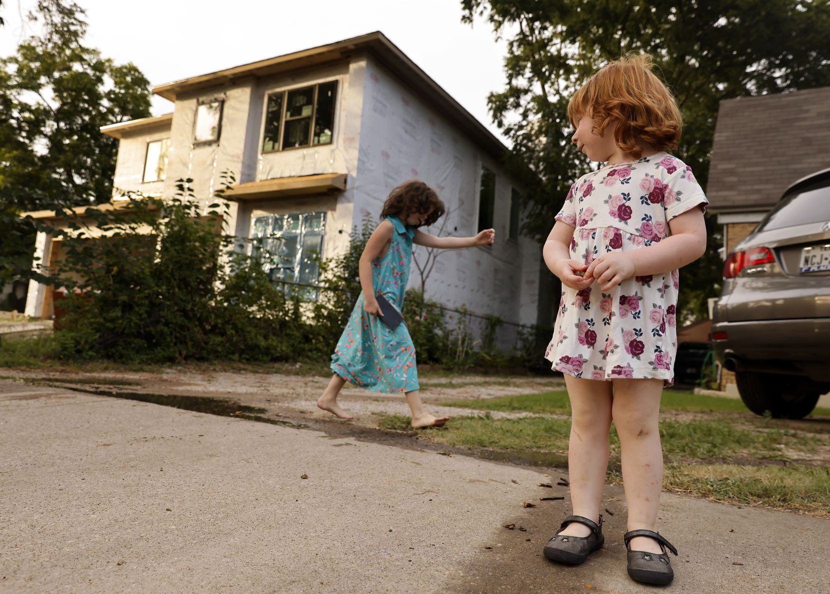 Opal Benjamin, 2, watches as her sister Ivy, 6, plays in their front yard next door to a large modern home under construction on Cristler Avenue in the Mount Auburn neighborhood of East Dallas.