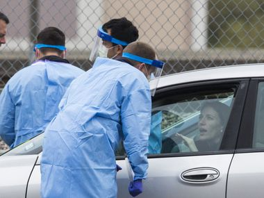 A motorists talks with staff at the drive-through coronavirus testing site at American Airlines Center in downtown Dallas on Saturday.