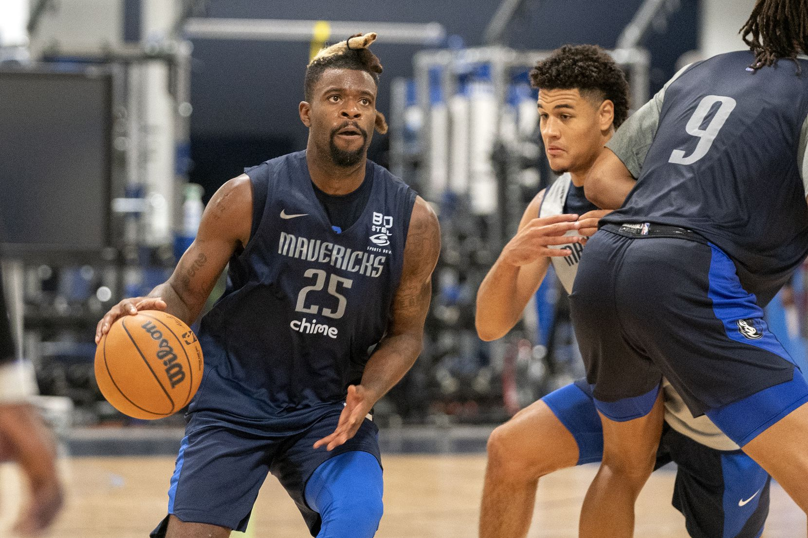 Dallas Mavericks guard Reggie Bullock (25) drives the lane as guard Josh Green tries to slide through the pick of center Moses Brown (9) in a scrimmage during the first practice of training camp Tuesday, September 28, 2021 at the Dallas Mavericks Training Center in Dallas.