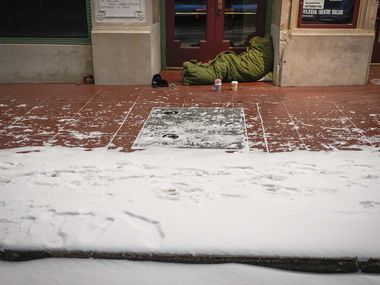 With temperatures already falling into the single digits homeless person sleeps in the doorway of the Majestic Theater as a winter storm brings snow and freezing temperatures to North Texas on Sunday, Feb. 14, 2021, in Dallas. (Smiley N. Pool/The Dallas Morning News)