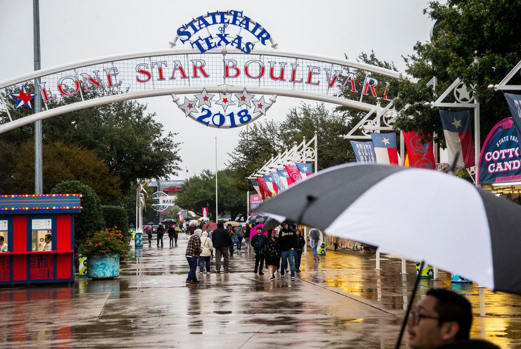Fair attendees walked in the rain last month during the State Fair of Texas at Fair Park. Coupon sales at the fair were down nearly $9 million versus last year after several days of gloomy weather during the fair's run.