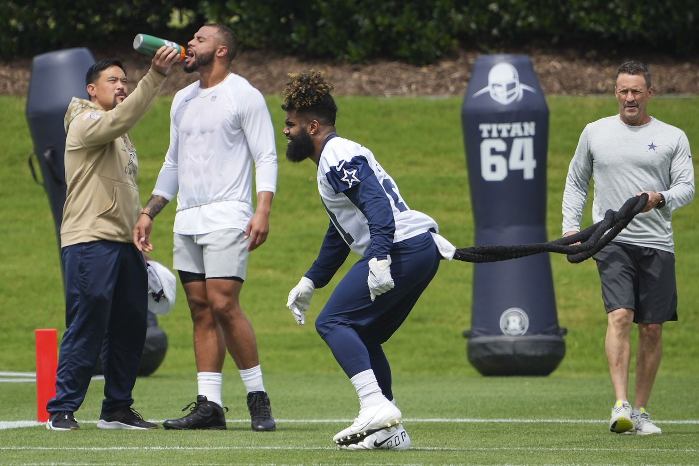 Dallas Cowboys running back Ezekiel Elliott (21) works with a resistance band as quarterback Dak Prescott gets a drink of water during a minicamp practice at The Star on Tuesday, June 8, 2021, in Frisco. (Smiley N. Pool/The Dallas Morning News)