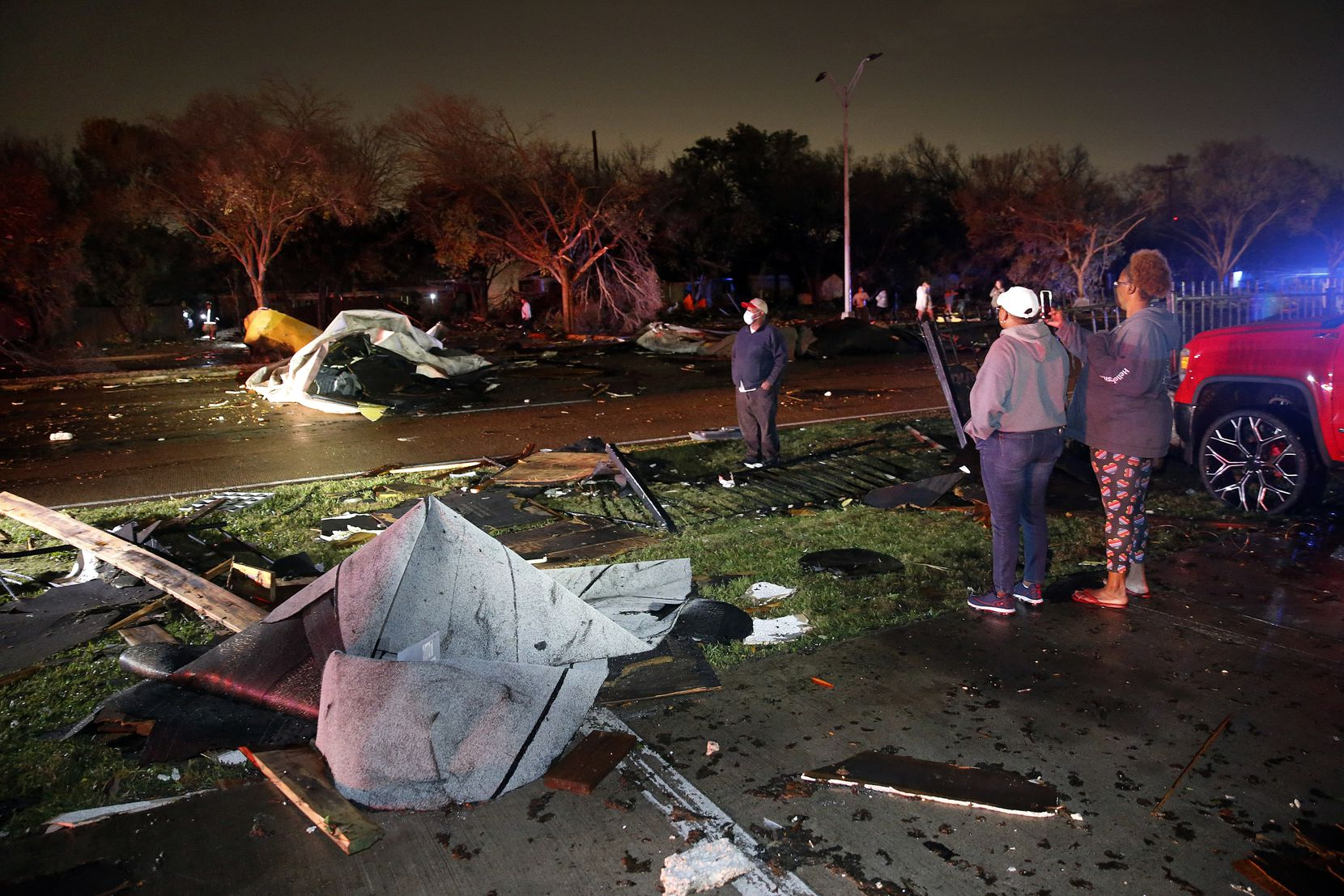 People inspect roofs of The Mirage Apartments that tore off and landed on Pioneer Parkway in Arlington following a tornado-warned storm, Tuesday night, November 24, 2020. (Tom Fox/The Dallas Morning News)