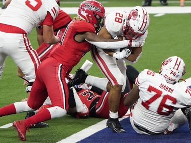 Katy running back Jalen Davis (28) scores on a 3-yard touchdown run past Cedar Hill middle linebacker Jaheim Lowe (10) during the first half of the Class 6A Division II state football championship game at AT&T Stadium on Saturday, Jan. 16, 2021, in Arlington, Texas.