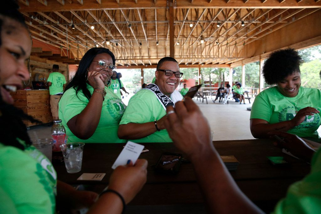 Trenton Johnson (center), a transgender man, sits with his fiancee Bridget Charleston (left) to play Cards Against Humanity with his friends during the Black Trans Advocacy Conference family day at Circle R Ranch in Flower Mound, Texas.