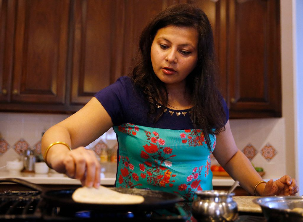 Sapna Punjabi-Gupta prepares to flip a roti at her home in Irving.