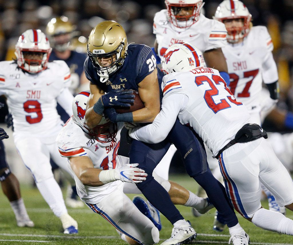 Navy Midshipmen wide receiver Keoni-Kordell Makekau (28) plows through Southern Methodist Mustangs safety Trevor Denbow (16) and safety Rodney Clemons (23) as he made a catch and run in the third quarter at Navy-Marine Corps Memorial Stadium in Annapolis, Maryland, Saturday, November 23, 2019. (Tom Fox/The Dallas Morning News)