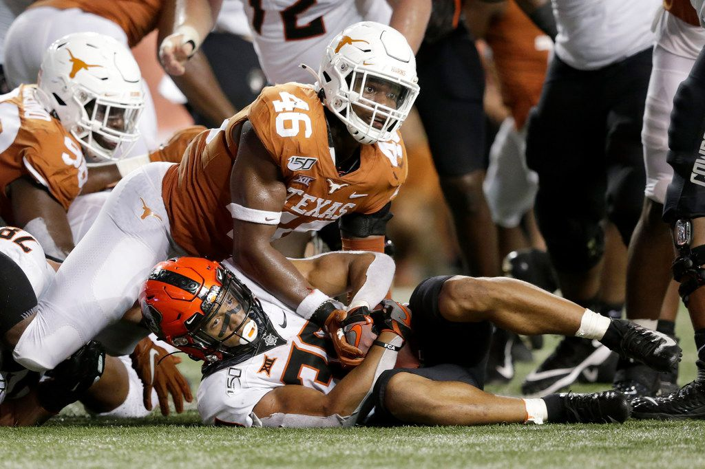 Chuba Hubbard #30 of the Oklahoma State Cowboys is stopped short on a fourth down by Joseph Ossai #46 of the Texas Longhorns in the second half at Darrell K Royal-Texas Memorial Stadium on September 21, 2019 in Austin, Texas.