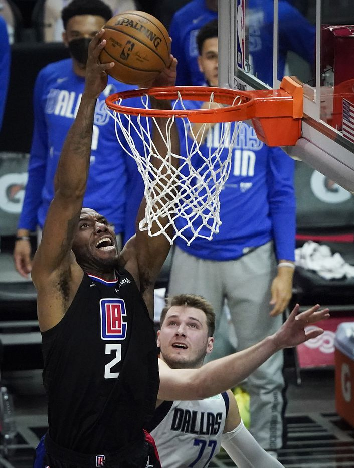 LA Clippers forward Kawhi Leonard (2) dunks the ball past Dallas Mavericks guard Luka Doncic (77) during the second half of an NBA playoff basketball game at Staples Center on Tuesday, May 25, 2021, in Los Angeles. The Mavericks won the game 127-121.