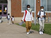 Jerrell Brown (left), 9, walks with Jayce Williams, 7, after a day of classes at Paul L. Dunbar Learning Center in Dallas. Dunbar made huge strides after instituting Dallas ISD's signature turnaround program, Accelerating Campus Excellence, which provides additional resources to struggling schools.