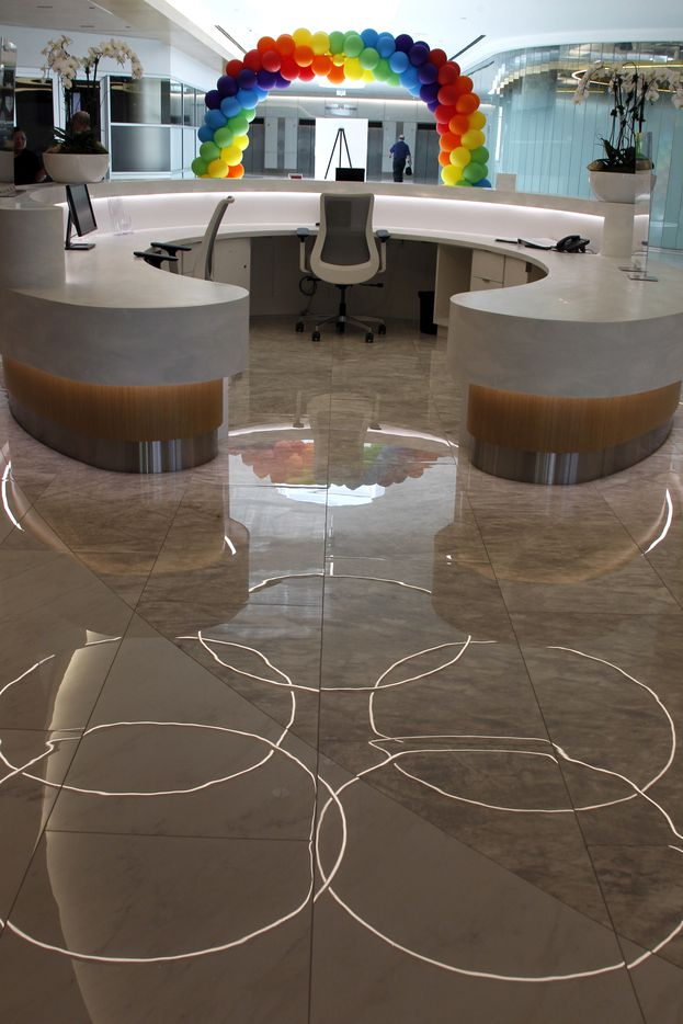 Illuminated rings are reflected in the floor surface just behind a welcome station centrally located to greet those entering the building from the parking garage.