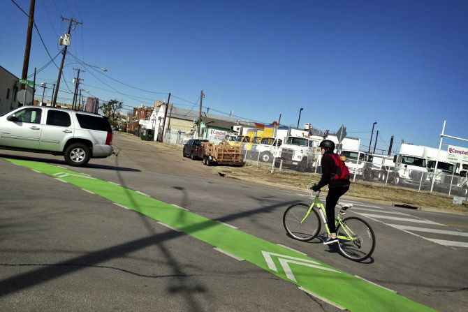A bicyclist makes her way across Main Street from Hill Avenue using new bike lanes and markings on Monday in Dallas' Deep Ellum neighborhood.