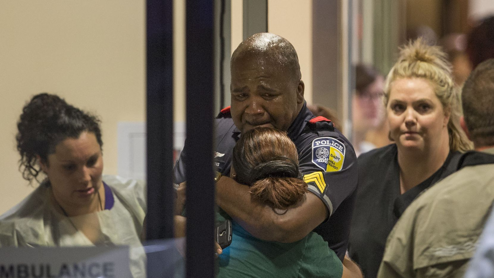 A DART (Dallas Area Rapid Transit) police officer receives comfort at Baylor University Hospital emergency room entrance on July 7, 2016 in Dallas, Texas. Dallas protestors rallied in the aftermath of the killing of Alton Sterling by police officers in Baton Rouge, La. and Philando Castile, who was killed by police less than 48 hours later in Minnesota.