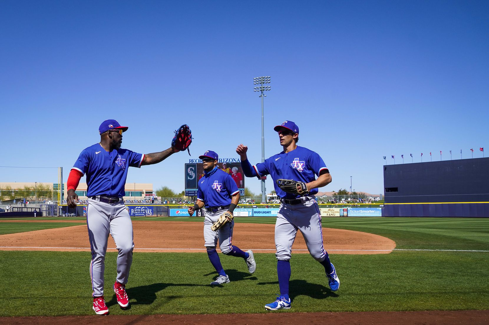 Texas Rangers center fielder Eli White (right) gets a hand from right fielder Adolis García as they leave the field with left fielder Jason Martin (center) after White made a running catch on a line drive by Seattle Mariners first baseman Jose Marmolejos to end the first inning of a spring training game at Peoria Sports Complex on Wednesday, March 10, 2021, in Peoria, Ariz.