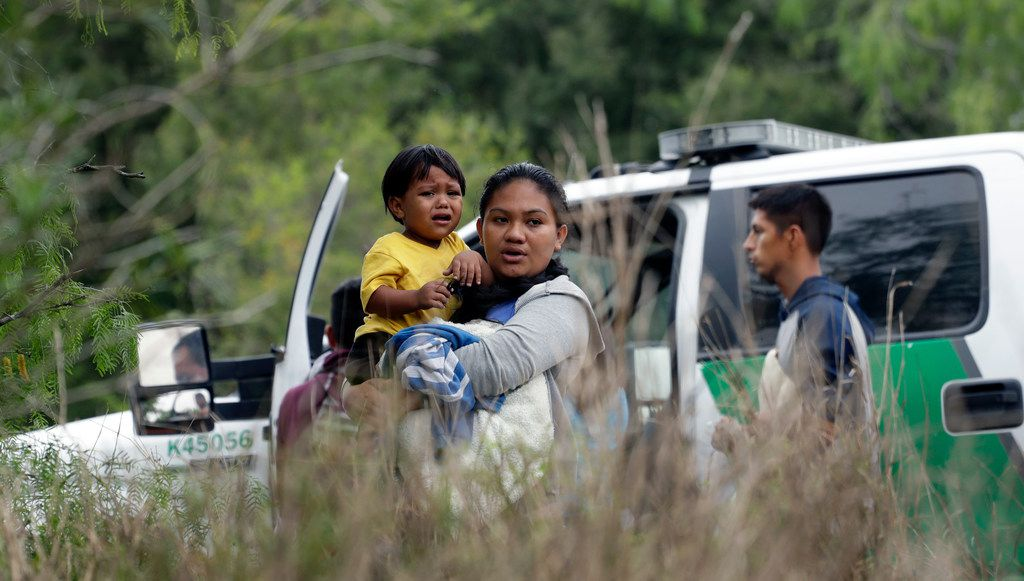 Wendy Johana Garcia Guzman holds her son William Josue Gonzales Garcia, 2, as they wait with other families who crossed the nearby U.S.-Mexico border near McAllen, Texas wait for order Patrol agents to check names and documents.