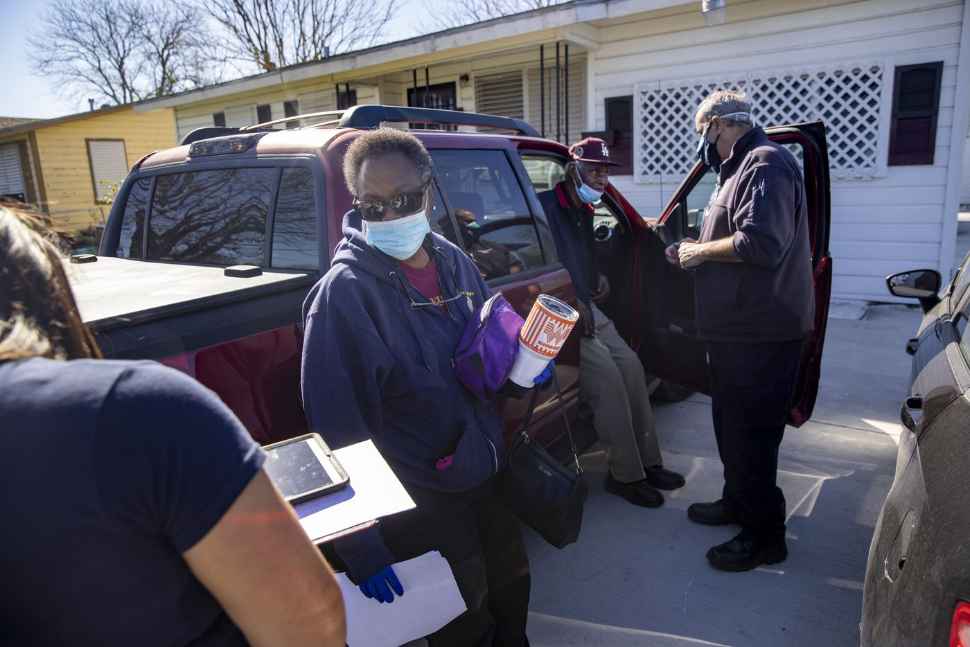 Firefighter I/EMT Kassandra Goce (left) surveys Evelyn Adams, 61, while Firefighter II/EMT Steve Bowers (right) prepares to administer the first dose of the Moderna COVID-19 vaccine to Adams and her father, Sam Johnson, 86, in their driveway in Corpus Christi, Texas, on Monday, Feb. 2, 2021. The Corpus Christi Fire Department has spearheaded a program for administering COVID-19 vaccines to vulnerable elderly populations through utilizing existing rosters kept by the city's Meals on Wheels initiative and those of other civil senior service programs. (Lynda M. González/The Dallas Morning News)
