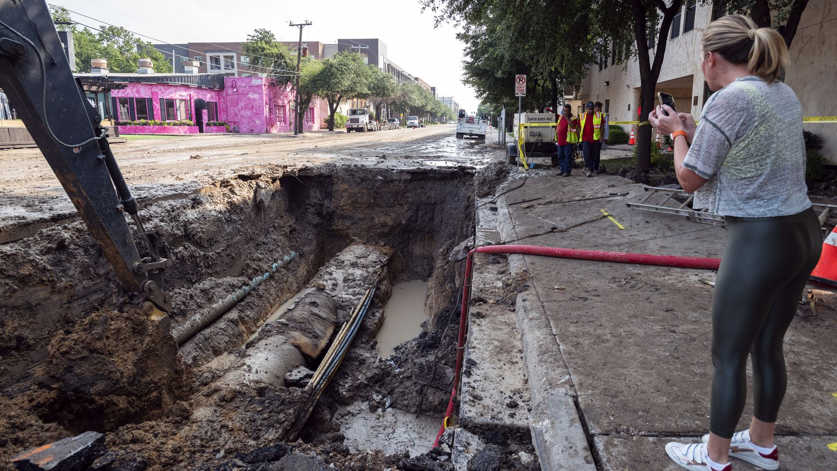 An astonished Carolyn Carmichael photographs the busted water main pipe Thursday, Aug. 5, 2021.