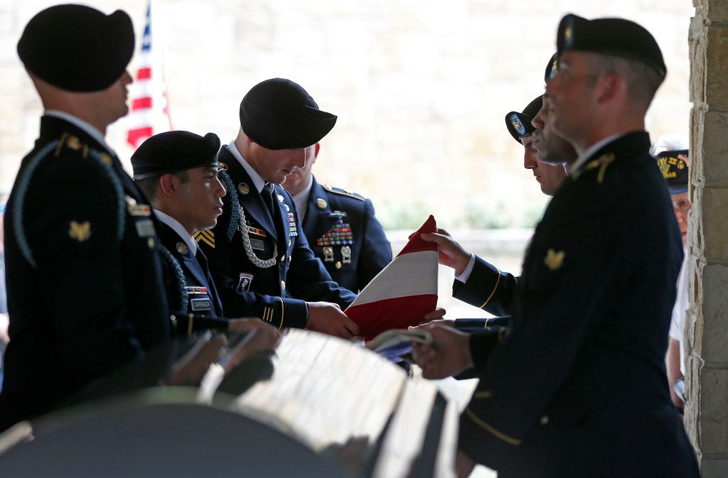 Members of the US Army Honor Guard fold an American flag that has wrapped over a casket of Army Pvt. Kenneth D. Farris killed during World War II in Germany during a burial ceremony at Dallas-Forth Worth National Cemetery in Dallas, Monday, July 9, 2018. Pvt. Farris has his remains identified on April 23, 2018.