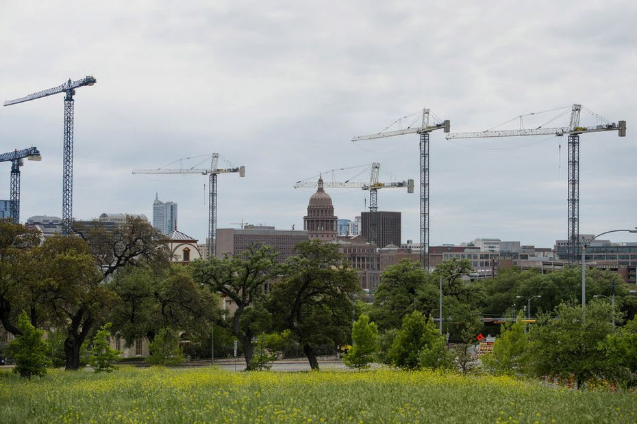 The Texas State Capitol building stands beyond construction cranes at the University of Texas at Austin campus this month. Cities in the West and Southwest are experiencing economic growth exceeding records set before the financial crisis as young, educated workers migrate west to create housing shortages and drive up wages. Moved Monday, April 27, 2015.