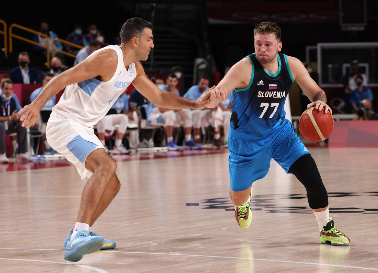 Slovenia's Luka Doncic (77) drives on Argentina's Luis Scola (4) in the first half of play during the postponed 2020 Tokyo Olympics at Saitama Super Arena on Monday, July 26, 2021, in Saitama, Japan. Slovenia defeated Argentina 118-100. (Vernon Bryant/The Dallas Morning News)