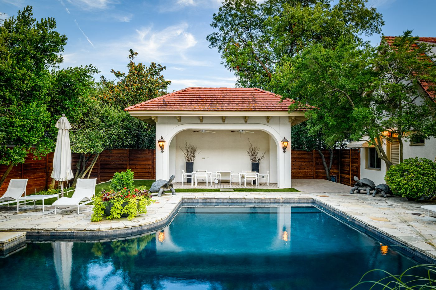 The swimming pool has a lap lane and is surrounded by lounging areas and a small casita.