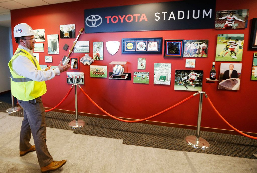 Hunt points out a few historical items on a wall outside the suites at Toyota Stadium.