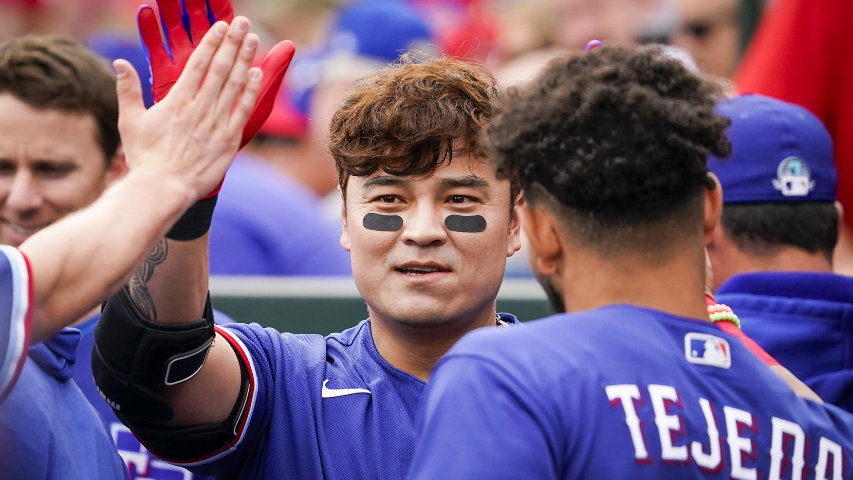 Texas Rangers outfielder Shin-Soo Choo high fives teammates in the dugout before a spring training game against the Los Angeles Angels at Tempe Diablo Stadium on Friday, Feb. 28, 2020, in Tempe, Ariz.